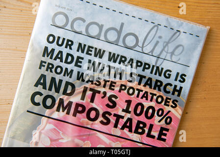 Ocado Life magazine in compostable cover or packaging on kitchen table - Stock Image