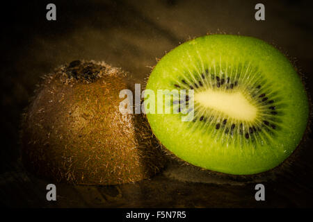 Fresh kiwi close up with drops of water on an old wooden table. - Stock Image