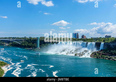 Looking toward the American falls at Niagara on a sunny day. The Maid In The Mist pleasure boat is visible at the foot of the falls on the river. - Stock Image
