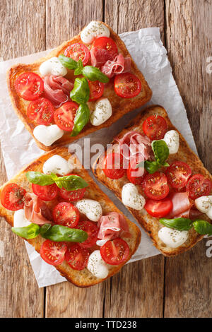 Italian open sandwiches with mozzarella, tomatoes, ham and basil closeup on the table. Vertical top view from above - Stock Image