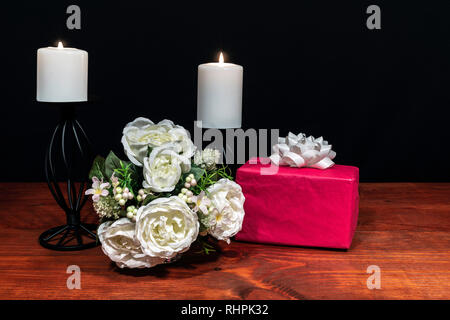 Beautiful bouquet of arranged flowers white candles on a holder with a present on a wooden table. mothers day, Easter, valentines, birthday, Christmas - Stock Image