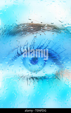woman eye behind a glass with drops of water - image for book cover - Stock Image