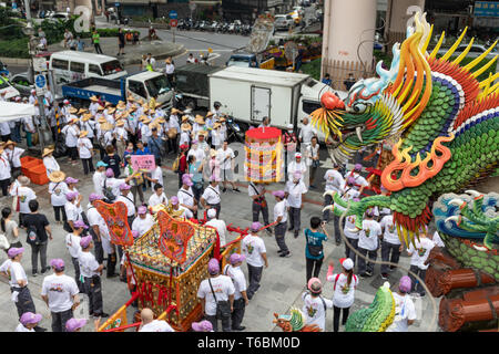 A week-day parade from a Mazu temple in Taipei brings traffic to a near standstill as devotees and performers well into the street. - Stock Image