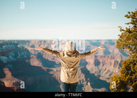 Rear view of woman with arms outstretched standing at Grand Canyon National park - Stock Image