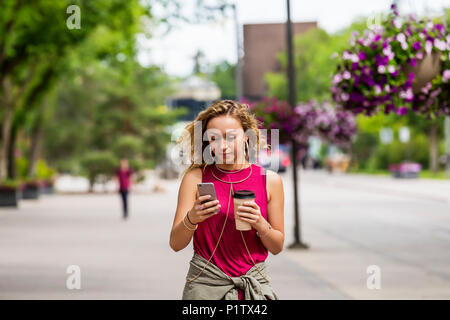 A young woman walking down a street near a university campus texting on her smart phone; Edmonton, Alberta, Canada - Stock Image