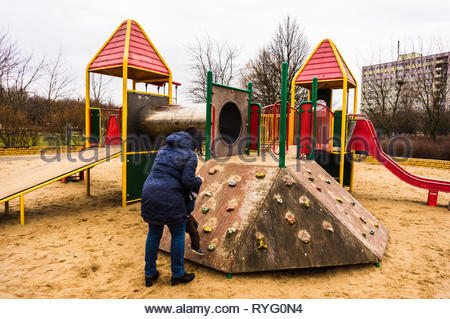 Poznan, Poland - March 3, 2019: Woman helping toddler boy on a wooden climb wall at a playground. - Stock Image