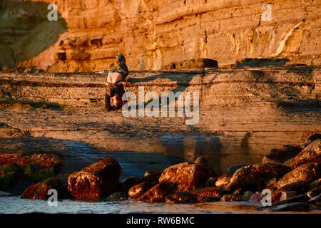 Beautiful young woman upside down in yoga pose throwing shadow on rugged cliffs at Sunset Cliffs Natural Park, Point Loma, San Diego, California, USA - Stock Image