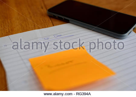 Lined paper with 'To Do' written on the top. Sticky note and black phone/ tablet used to create lists and plan. All items on wooden table. - Stock Image