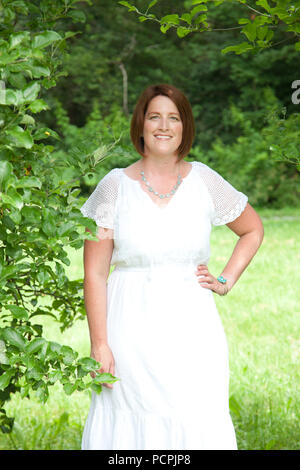 A red haired woman stands and smiles for a lovely portrait in a white dress outside - Stock Image