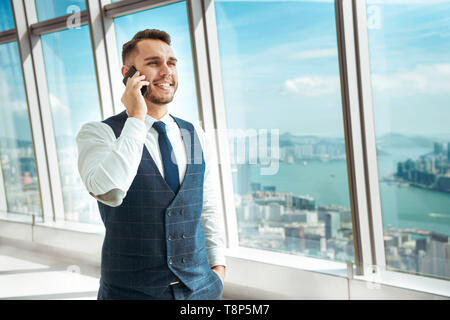 Successful businessman speaks by mobile phone against big city - Stock Image
