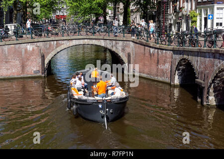 Tourists on a boat on the Keizersgracht canal in Amsterdam, Netherlands - Stock Image
