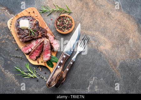 Medium rare Ribeye steak with herbs and a piece of butter on the wooden tray. Top view. - Stock Image