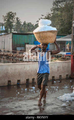 Man carrying a whicker basket full of ice on Indian fish docks. - Stock Image
