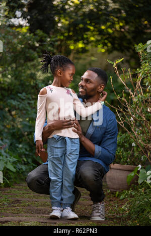 A man sitting on his haunches to look at his young daughter - Stock Image