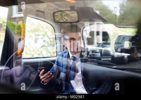 Young businessman in back of London taxi, seen through glass - Stock Image