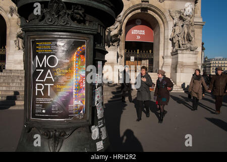 Winter visitors by the Opera Garnier and iconic Paris advertising column. - Stock Image