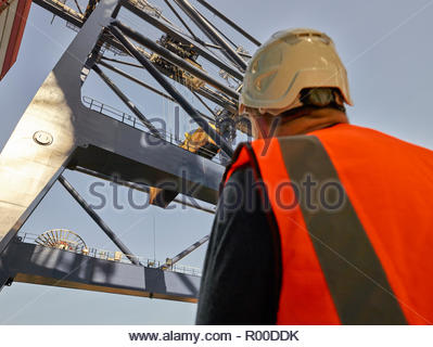 Low angle view of dock worker beneath crane at Port of Felixstowe, England - Stock Image