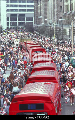 Looking down on London red single decker buses at crowd of people in foil blanket Mars marathon runners collect clothing from bus 1980s England UK - Stock Image