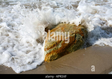 The sandy coast of the sea, on which there is a large stone and this one is exposed to  water of sea waves of the - Stock Image