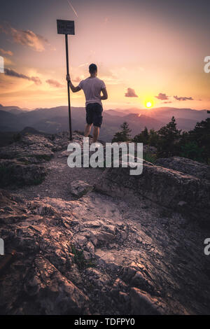 Man on top of mountain. Conceptual scene on Hohe Wand in Austria during Sunset - Stock Image