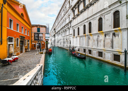 A Venetian gondolier with a family of tourists in his gondola, steers past a small square near the Bridge of Sighs in Venice, Italy - Stock Image