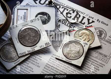 Coin Collecting - Various Coins - Morgan Dollars - Ike Dollar - Trade Dollar - against backdrop of the Greysheet with magnifiers - Stock Image