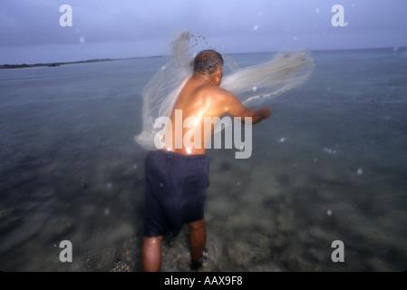 Net Fisherman throwing net in the rain Marshall Islands - Stock Image