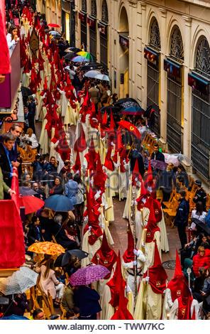 Hooded Penitents (Nazarenos) in the procession of the Brotherhood (Hermandad) La Lanzada, Holy Week (Semana Santa), Seville, Andalusia, Spain. - Stock Image