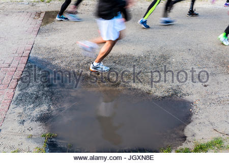 Runners marathon running next to puddle with reflection - Stock Image