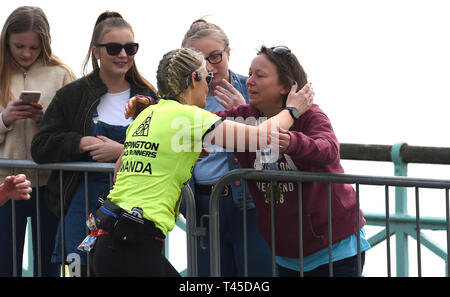 Brighton UK 14th April 2019 - A runner gets a hug as  thousands of runners some in fancy dress take part in this years Brighton Marathon which is celebrating its 10th anniversary Credit: Simon Dack/Alamy Live News - Stock Image