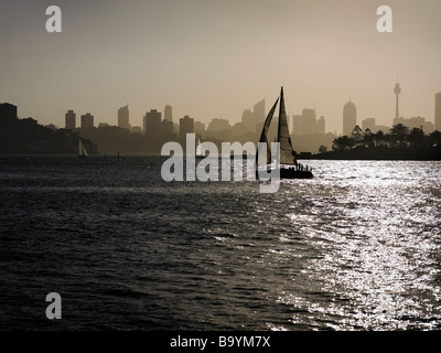 Yacht sailing through Sydney Harbour - Stock Image