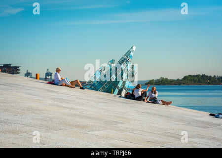 Oslo summer, view in summer of people relaxing on the Oslo Opera House waterfront with a floating glass sculpture titled She Lied in the background. - Stock Image