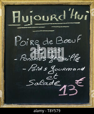 Menu blacboard outside a French restaurant. In French handwritten is announced what the menu of the day will be - Stock Image