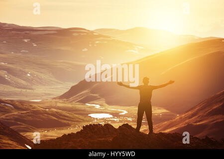 Happy man in winner pose at mountains top - Stock Image