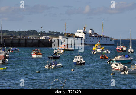 View across the harbour at Hugh Town, St Mary's,Isles of Scilly. Scillonian III  leaving the quay on its journey to Penzance.Cornwall UK - Stock Image