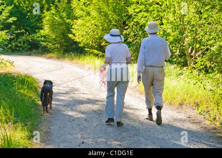 Senior couple walking a dog. - Stock Image