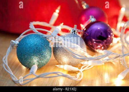 Purple, blue and silver round ornaments and lights - Stock Image