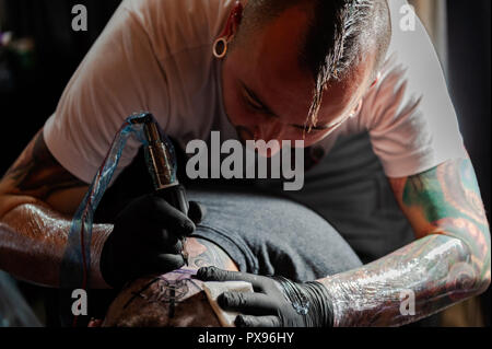 Skibbereen, West Cork, Ireland. 20th Oct, 2018. A tattooist tattos the back of a head during the tattoo show. The show has been attended by many tattooists from across Ireland and the North. The event finishes tomorrow. Credit: Andy Gibson/Alamy Live News. - Stock Image