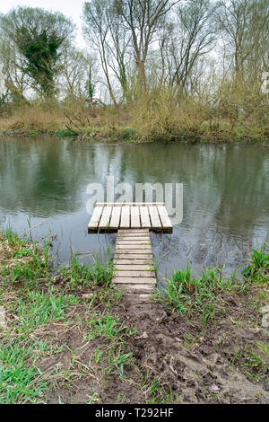 Small wooden jetty at the edge of a river - Stock Image