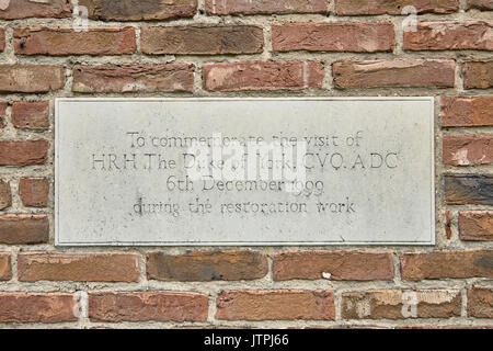 Plaque inset into brick wall commemorating opening of restored Nether Poppleton Tithe Barn, originally built in the 16th Century. - Stock Image