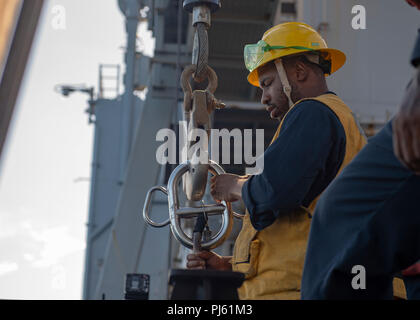 180901-N-AT530-0033 ATLANTIC OCEAN (Sep. 1, 2018) – Boatswain's Mate 2nd Class Keith Blair connects a crane to a Rigid Hull Inflatable Boat during small-boat operations on the amphibious dock landing ship USS Fort McHenry (LSD 43) during Carrier Strike Group FOUR (CSG 4) Amphibious Ready Group, Marine Expeditionary Unit exercise (ARGMEUEX). Kearsarge Amphibious Ready Group and 22nd Marine Expeditionary Unit are enhancing joint integration, lethality and collective capabilities of the Navy-Marine Corps team through joint planning and execution of challenging and realistic training scenarios. CS - Stock Image