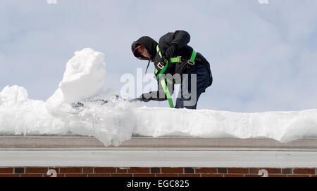 Lexington, MA, USA, 21 Feb, 2015. A workman cleaning snow from the roof of a three story apartment building in Lexington, - Stock Image