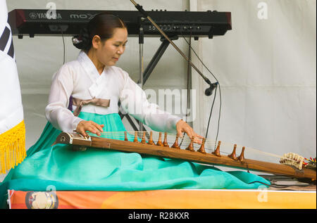 A female musician dressed in a hanbok plays a gayageum at the Korean Culture and Food Festival in Adelaide, South Australia, Australia. - Stock Image