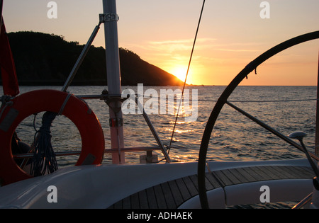 Sunset taken from the back of a yacht through the  wheel, no people - Stock Image