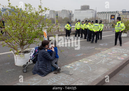 Police officers and Climate Change activists with Extinction Rebellion campaign for a better future for planet Earth after blocking Waterloo Bridge and as part of a multi-location 5-day Easter protest around the capital, on 16th April 2019, in London, England. - Stock Image