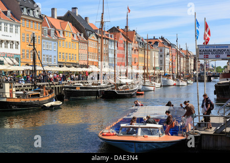 Tourists on canal tour boat with old boats moored in front of colourful buildings in Nyhavn harbour Copenhagen Zealand - Stock Image