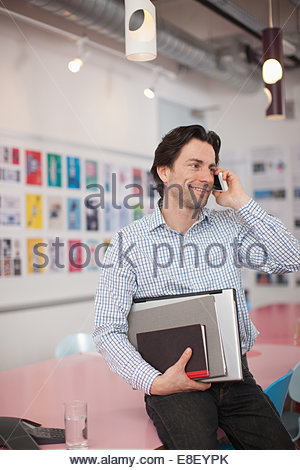 Smiling businessman holding laptop and books talking with cell phone  in office - Stock Image