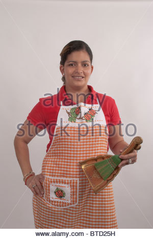 Maid poses with whisk broom and dustpan. - Stock Image