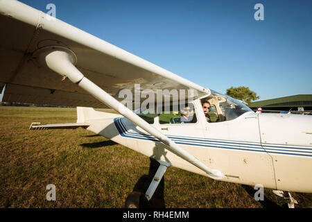 Father and son in small airplane in sunny field - Stock Image