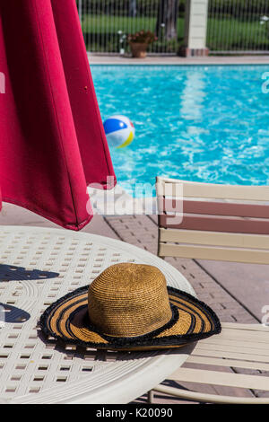 Womans summer hat on a poolside table of a community pool with a colorful beachball floating in the crystal clear water on a hot summers day California - Stock Image
